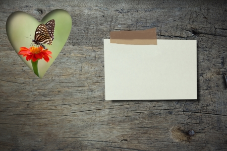 feeding through: Note paper  on grunge wood board with  Zinia flower and butterfly background Stock Photo