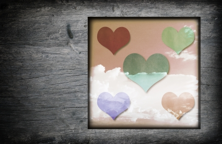 Vintage wood frame with hearts icon and blue sky white clouds  image background photo