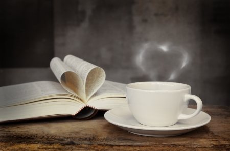 Still life with cup of coffee and book on grunge wood table in vintage style photo