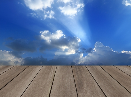 Grunge wood floor with blue sky white clouds background  photo