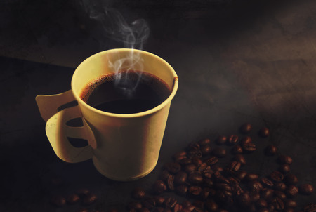 Steaming paper coffee cup and beans in vintage style photo