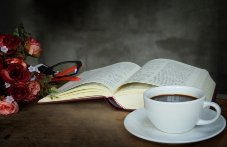 Still life cup of coffee,roses and book on old wooden table  photo