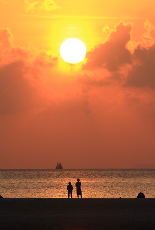 Beach  silhouettes of people relaxing at sunset photo