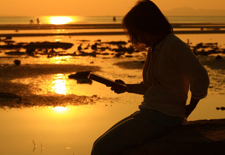 Silhouette woman reading book by beach at sunrise photo