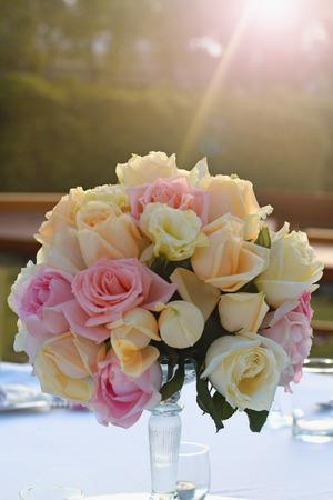 Roses bouquet arrange for wedding table decoration in garden photo