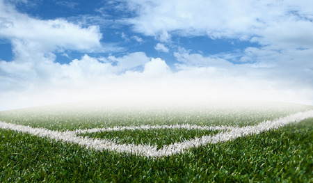 Corner soccer green grass field with blue sky white clouds background photo