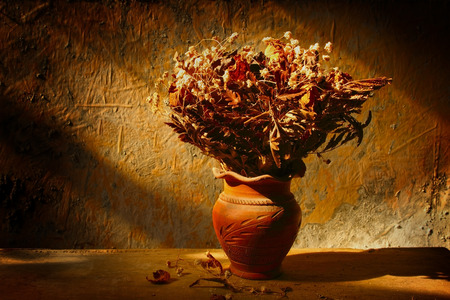 Still life with bouquet of dried roses in clay vase with grunge background photo