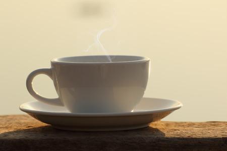 tarde de cafe: Tarde taza de caf� en la tabla de madera con efecto de luz dorada Foto de archivo