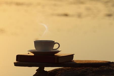 tarde de cafe: Tarde taza de caf� y libro sobre tabla de madera con efecto de luz dorada