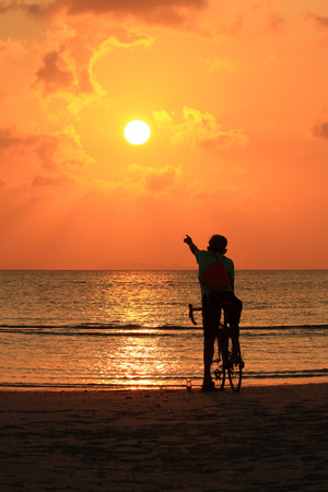 Silhouette of a biker  on the beach point to  sunset photo