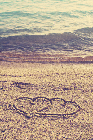Heart shape icon  drawn on beach sand in vintage style photo