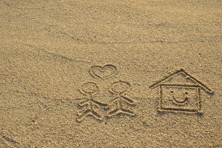 Happy lover and house with heart shape drawn on beach sand photo