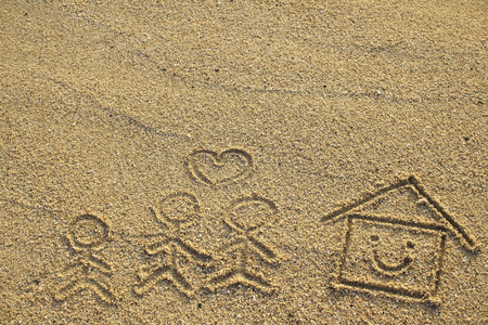 Happy family and house with heart shape drawn on beach sand photo