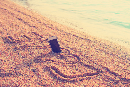 Modern smart phone on the beach with love text photo