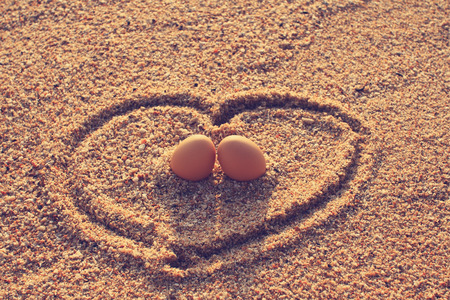 Happy lover eggs setting on beach with golden sunrise in vintage style photo