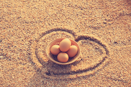 Easter eggs in bamboo basket on beach  in vintage style photo
