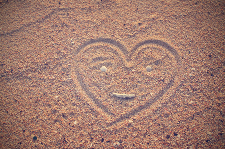 Heart shape drawn on beach sand  photo