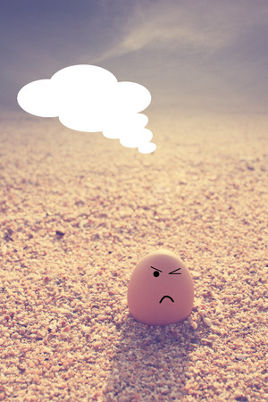 Angry egg  sitting on beach and  speech talk with vintage filter effect photo