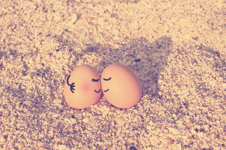 Happy lover eggs sitting on beach with vintage filtered effect photo