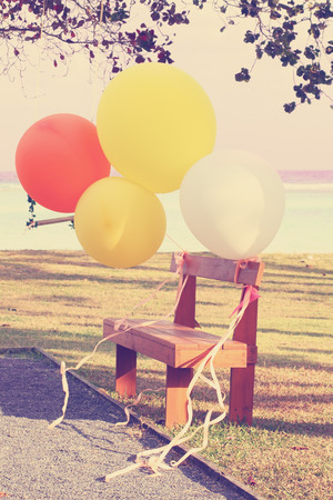 Colorful balloons and wood chair in garden with vintage filter effect photo
