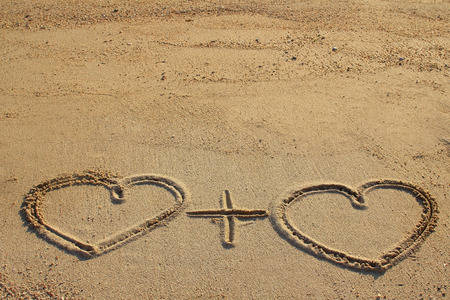 Couple of hearts shape drawn on beach sand photo