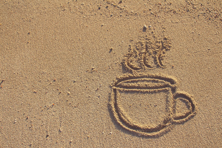 Vintage coffee cup  drawn on sand beach,filtered image