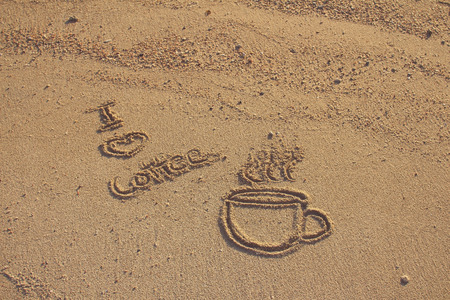 Vintage love coffee cup  drawn on sand beach,filtered image photo