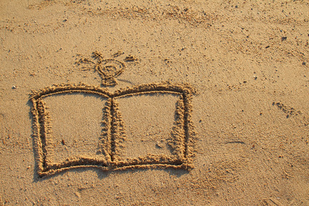 Book and light bulb drawn on sand beach