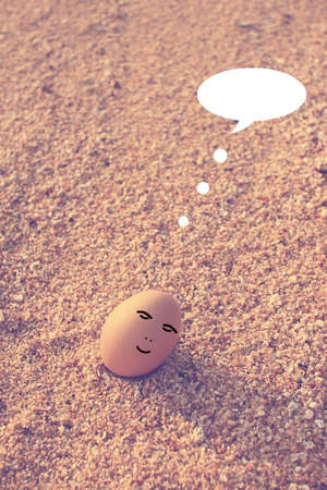 Happy egg sitting on beach with bubble talk in vintage filter effect photo