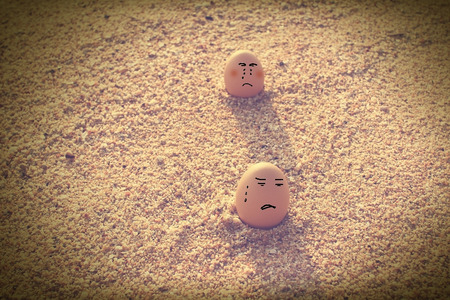 Broken heart lover eggs sitting on beach with vintage filter effect photo
