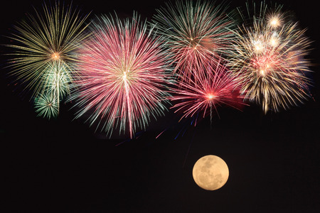 Colorful fireworks and full moon  over black background photo