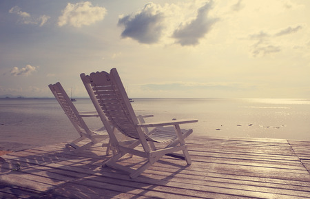 White wooden beach chair facing seascape,vintage filter effect photo