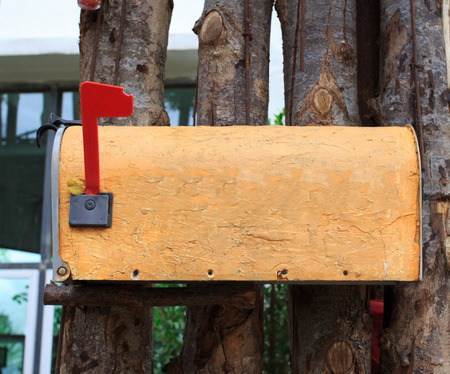 Old yellow mailbox on wood fence outdoor photo