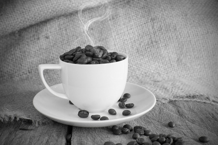 Vintage cup of roasted coffee beans in black and white tone photo