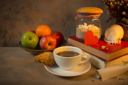 Still life coffee breakfast,apples and old book with seashell decoration photo