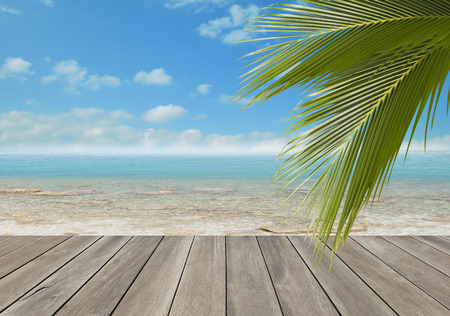 Wood plank over beach with coconut palm tree leaf photo