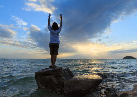 Woman hand show victory sign on rock beach at dawn