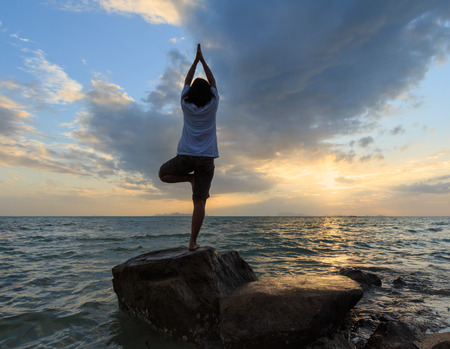 Silhouette yoga girl by the beach at sunrise doing standing tree pose  photo
