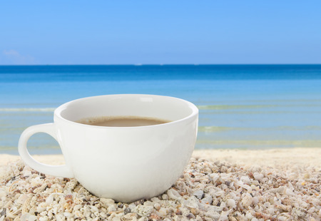 Morning coffee cup on seashell beach background Stock Photo