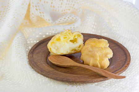 creampuff: Choux buns or Eclair on wood dish and crochet  white background  Stock Photo