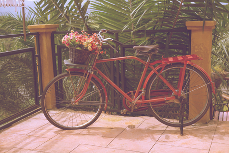 decorated bike: Vintage red bicycle with a bucket of colorful flowers