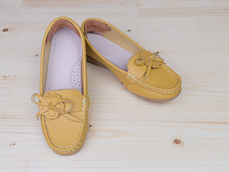 flat shoes: Yellow casual leather flat shoes  on wooden background Stock Photo