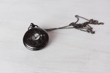 grune: Classic pocket watch on white grune wooden board Stock Photo