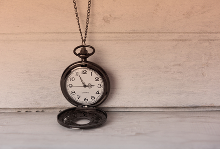 grune: Classic pocket watch on white grune wooden background with filter vintage effect