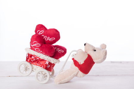 sweet heart: Cute teddy bear carry love heart items on white bicycle