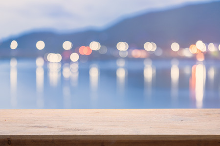 emty: Colorful blur bokeh  night lights over sea with emty wood floor