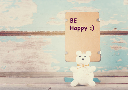 wrote: Be happy wrote paper stand and cute bear on grunge blue wooden background Stock Photo