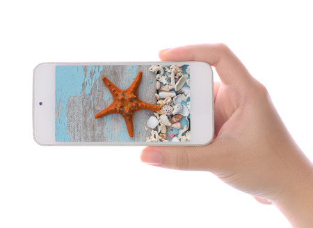 star fish: Hand using smartphone photographed star fish and sea shell isolated on white background