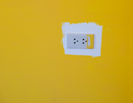 electrical plug: New electrical plug on yellow wall background Stock Photo