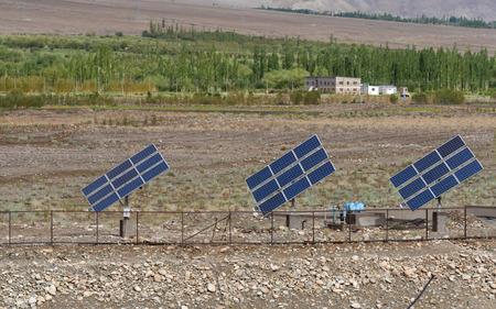 arbol alamo: Field with rows of blue solar panels in grassland with poplar tree  background in Jammu-Kashmir,India Foto de archivo